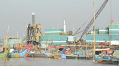 Tele view through small fishing boats with industrial barge on Mekong river Stock Footage