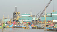Stock Video Footage of Tele view through small fishing boats with industrial barge on Mekong river