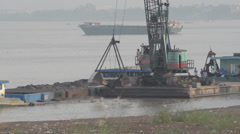 CONSTRUCTION DREDGING: Crane shovels sand from river with boat nearby Stock Footage
