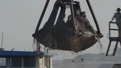 CONSTRUCTION DREDGING: Giant scoop lifts sand and mud from river to barge - stock footage
