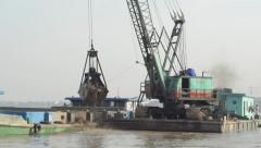 CONSTRUCTION DREDGING: Crane scoops sand from river in giant bucket Stock Footage