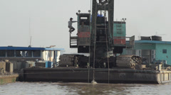 CONSTRUCTION DREDGING: Crane on barge scoops sand from river Stock Footage