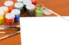 paints with brushes and empty white paper sheet - stock photo