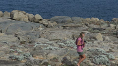 Zoom out from a Girl walking in Torndirrup National Park Stock Footage