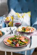 salad with salmon and verdure in plate on table with blue chair background - stock photo