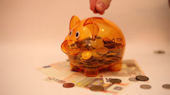 Saving money, putting coins in a piggy bank, debts, currency, Euro banknotes Stock Footage