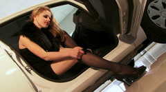 Magnetic model is putting on her black hosiery in a cool car. Stock Footage