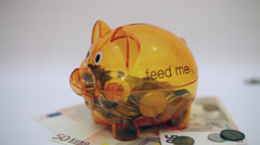 Saving money, putting coins in a piggy bank, debts, currency, Euro banknotes - stock footage