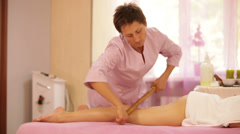 Massage therapist massaging female legs with bamboo stick at beauty salon Stock Footage