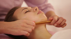 Massage therapist doing massage of female face with bamboo stick at beauty Stock Footage