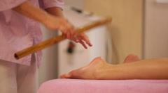 Massage therapist massaging woman's feet with bamboo stick at beauty salon. Stock Footage