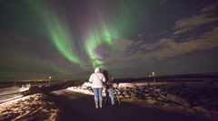 A man and woman viewing colorful aurora (northern lights) in Iceland.  Stock Footage