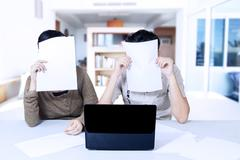Couple hiding behind paper at home Stock Photos