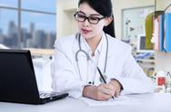 Stock Photo of female doctor writes a prescription