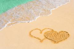 Drawing connected hearts on beach - stock photo