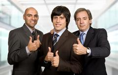 thumbs up of three businessmen at the office - stock photo