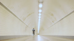 Cyclist Rolls Out in Long Lit Up Tunnel in Slow Motion - 29,97FPS NTSC Stock Footage