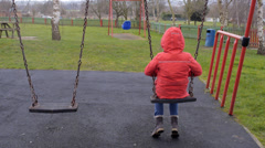 Lonely girl on swing in park Stock Footage
