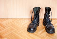 old used black bovver boots on parquet floor - stock photo