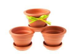 Three small clay flower pots with saucers - stock photo