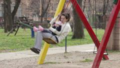 Mother and child swinging toghether on the playground in the park Stock Footage