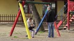 Mother and father swinging baby girl on the playground,medium shot - stock footage