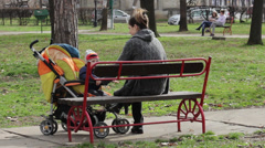 Mother and child sitting on the bench in the park,mother rocking stroller Stock Footage