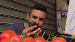 Man carefully examines eggplants in the market Stock Footage
