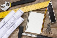 Stock Photo of technical drawing and tools with blank notebook