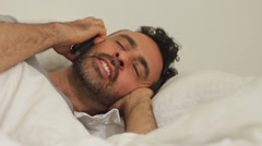 Man in bed talking on the phone Stock Footage