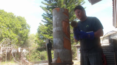 Native American man carving a design into a log-wide shot Stock Footage
