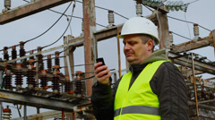 Electrician with cell phone in the electric substation - stock footage