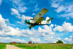 agricultural aircraft flying low over a field - stock photo