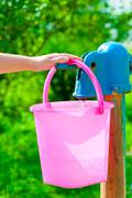 female hand pours water on a column in a bucket - stock photo