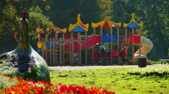 Public garden with flowerbeds and playground for kids Stock Footage