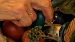 Elderly woman arranges Easter eggs in a basket Stock Footage