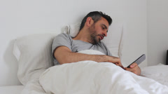 Man use tablet in bed to stay updated Stock Footage