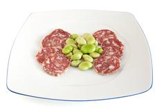 dish with fava beans and salami slices - stock photo