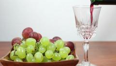 Red Wine Pouring Into A Glass. Grapes. Stock Footage