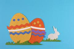 Colorful eggs with grass and rabbits drawn and cut on paper, easter egg on a Stock Photos
