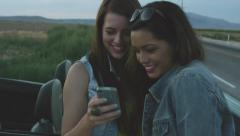 Stock Video Footage of 2 Girls Look At A Phone And Smile
