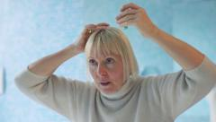 Senior woman at home, using hair lotion - stock footage