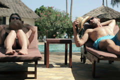 Couple cooling with summer hats on hot day by the pool NTSC Stock Footage