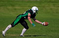 A young, football player about to catch the ball. Stock Photos