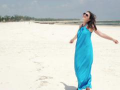 Happy woman turning round on the beach NTSC Stock Footage