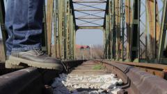 Man jumps rails on the railway, the railway bridge in the background. Low angle. Stock Footage