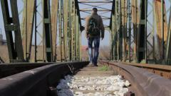 Young man walking on railroad tracks and cross the railway bridge.Low angle view Stock Footage