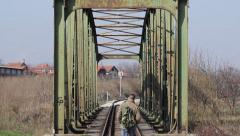Young man walking on railroad tracks and cross the railway bridge. Medium shot. Stock Footage