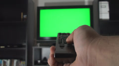 Man Hand With TV Remote Switching Channels On A Green Screen TV Point Of View Stock Footage