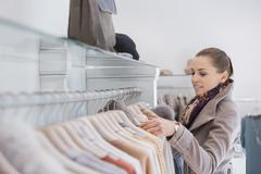 Stock Photo of side view of young woman choosing sweater in store
